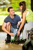 Young smiling couple preparing for rollerblades on bench at park