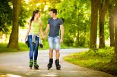 Young love couple spending free time  together, roller-skating in the park