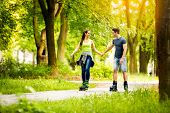 Young sporty couple ride rollerblades  and enjoying in nature