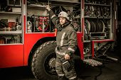 stock photo of firefighter  - Fireman taking equipment from firefighting truck - JPG