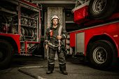 image of firefighter  - Firefighter near truck with equipment with water water hose over shoulder - JPG