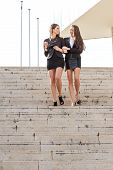 Two pretty businesswoman talking down the stairs