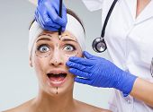 Beautiful woman face with surgical markings when startled look