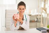 Portrait Of Smiling Medical Doctor Woman Showing Piggy Bank