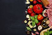 Italian ingredients - pasta, vegetables, spices, cheese - on dark background