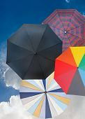 Four Different Open Umbrellas With Dark Blue Sky