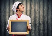 Handsome cook holding blank chalk board. Place for text