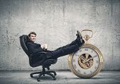 Young handsome businessman sitting in chair with cup