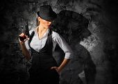 Woman with gun on grey wall background