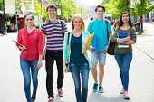 Full length of happy college students walking together