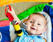 Happy and curious infant baby boy playing on activity mat