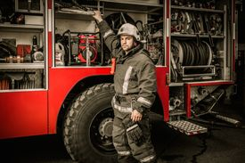 foto of firemen  - Fireman taking equipment from firefighting truck  - JPG