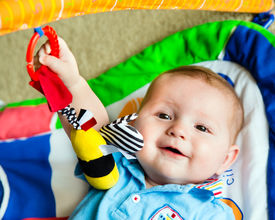 picture of playmate  - Happy and curious infant baby boy playing on activity mat - JPG