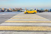 pic of pedestrian crossing  - taxi at yellow and white crossing zebra of pedestrian crosswalk on urban street
