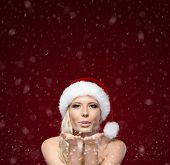Attractive woman in Christmas cap blows kiss, isolated on purple