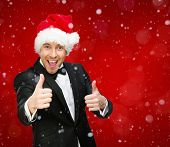 Half-length portrait of businessman wearing Santa Claus cap who thumbs up. Concept of holidays and Christmas