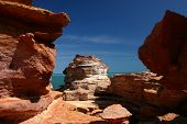 Red rock formations framimg turquoise sea and blue sky