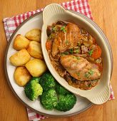 Chicken casserole served with roast potatoes and broccoli.