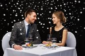 food, christmas, holidays and people concept - smiling couple eating main course at restaurant over black snowy background