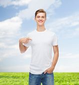 gesture, advertising, summer vacation and people concept - smiling young man in blank white t-shirt pointing finger on himself over natural background