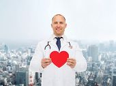 medicine, profession, charity and healthcare concept - smiling male doctor with red heart and stethoscope over city background