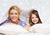 family, children, comfort, bedding and home concept - happy mother and girl under blanket over snowflakes background