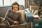 Young Woman Laying On Couch And Listening Music Listening Music In Headphones In Loft Apartment