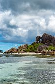 Enchanting Tourist Destination with Clear Blue Green Water Lagoon and Large Rock Forms on the Landscape in Seychelles Island. Captured with Stormy Sky Above. poster