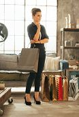 Full Length Portrait Of Young Woman With Shopping Bags In Loft A