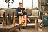 Relaxed Young Woman With Shopping Bags Sitting In Loft Apartment