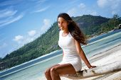 picture of beachfront  - Close up Young Attractive Woman Wearing White Casual Outfit Sitting on Dry Tree Branch at the Beachfront - JPG