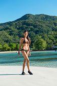 Sexy girl in Bikini standing at white sand beach