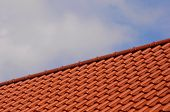 foto of red roof tile  - Red roof tiles on a house roof - JPG