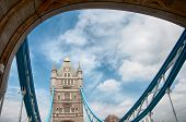 Detail of a tower on the Tower Bridge crossing the River Thames, London showing the suspension cables and historical stone facade against a cloudy blue sky