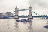 Small Vintage Boats at River Thames in London with Famous Historic Tower Bridge Background.