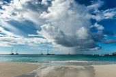 Dramatic storm clouds gathering over Anse Lazio Beach in the Sechelles with yachts and pleasure boats moored offshore