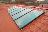 image of red roof  - Solar water heating system (geliosystem) on the red house roof.