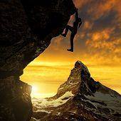 Silhoutte of girl climbing on rock at sunset. In the background Matterhorn - Swiss