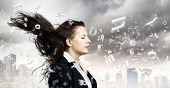 Young businesswoman with closed eyes and wind blowing in her face