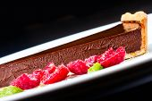 Chocolate Dessert With Raspberry. Dark Chocolate Cake With Chocolate Sauce On A White Plate, Macro
