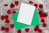 Christmas card envelope and letter with flower petals against antique netting and wood background