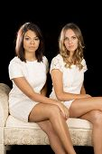 Two Women On Couch White Dresses