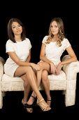 Two Women White Dress On Black Facing Legs Crossed