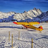 Yellow Red Airplane At The Mountain Ski Resort Airfield In Swiss Alps