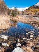 Small alpine mountain pond in fall - Val Ferret, Courmayer, Val d'Aosta, Italy, Europe.
