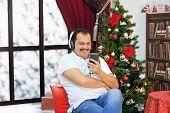 Man Listening To Music On Headphones  Near  Christmas Tree