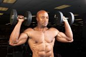 stock photo of weight lifter  - Toned and ripped lean muscle fitness man lifting weights - JPG
