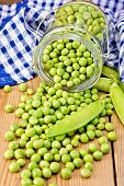 Green peas in glass jar with cloth on board