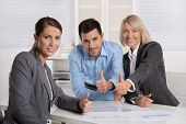 Successful business team: man and woman making thumbs up gesture sitting in the office.