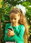 Girl sits in park and plays with cell phone